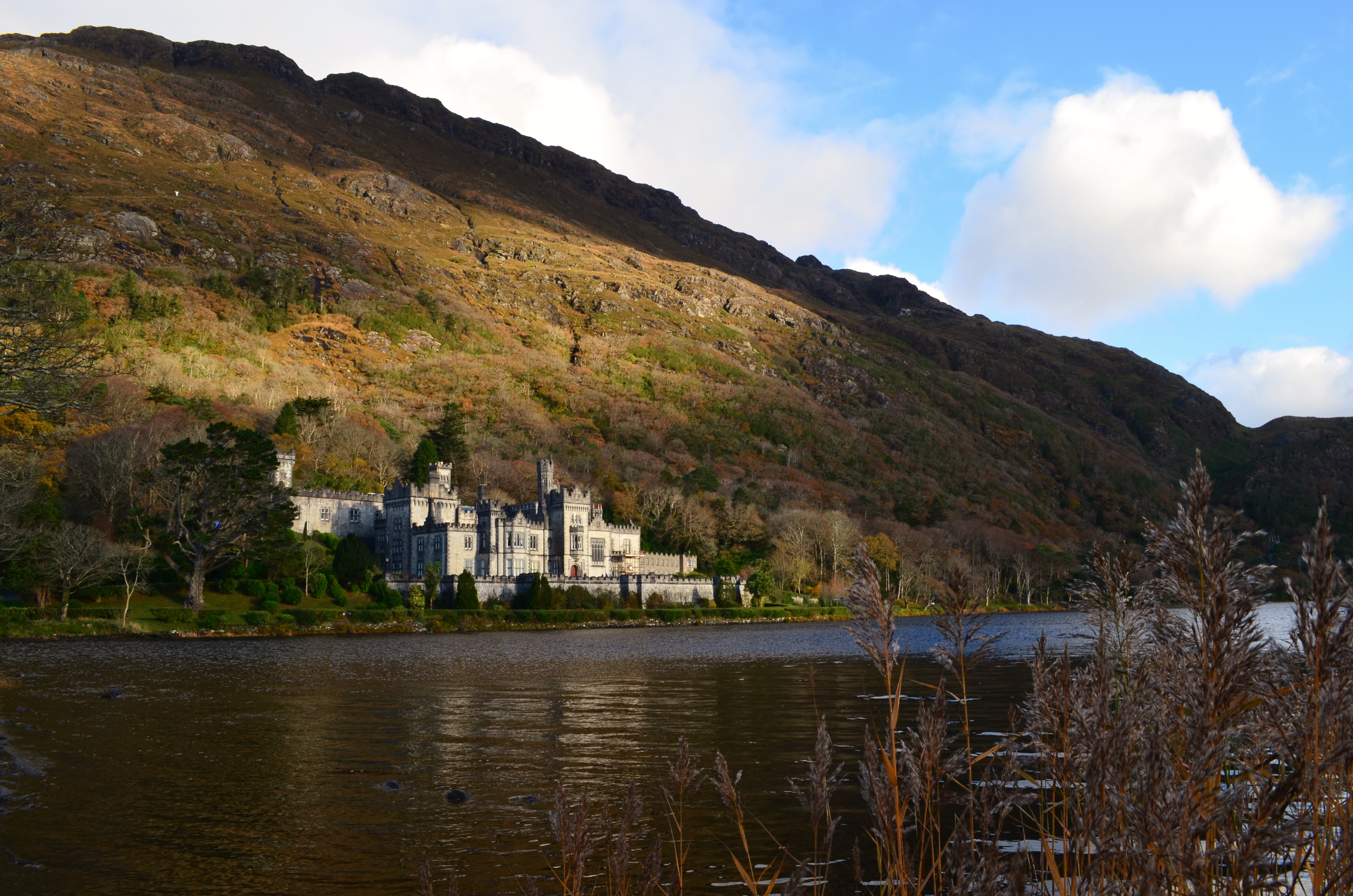 Sun catching the turrets of Kylemore Abbey across Lough Pollacapall